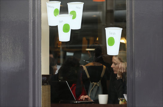 A woman looks at a laptop while sitting in a Starbucks in London