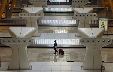 A passenger pulls her bag through an empty baggage claim lounge at Madrid's Barajas airport