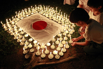 Students light candles as they pray for Japan's earthquake and tsunami victims during a ceremony at the Sathira-Dhammasathan Buddhist meditation centre in Bangkok