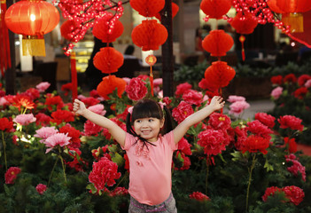 Child poses for photographs in front of Chinese New Year decorations in one of Kuala Lumpur's largest shopping malls