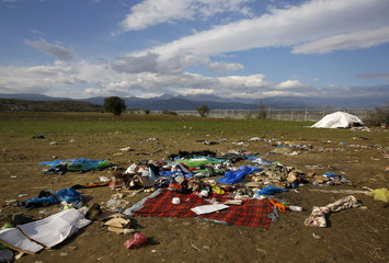 Clothing and sheets discarded by migrants are seen scattered on a field near a border fence, next to a makeshift camp by the Greek-Macedonian border close to the Greek village of Idomeni