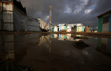Palestinian who lives in a container as a temporary replacement for his house that was destroyed in the 2014 war walks next a flooded path on a rainy day in Beit Hanoun