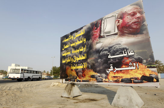 A banner showing tires burning on street and an unidentified injured man with the text ''Murder and destruction are terrorist acts that violates human rights'' set up by the Sharghi family is seen in Budaiya west of Manama