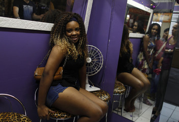 A woman poses for a photo after having hair extensions of a style called Megahair at a hair salon in a local market in Rio de Janeiro