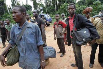 Displaced cocoa farmers from the village of Baleko-Niegre stand with their belongings