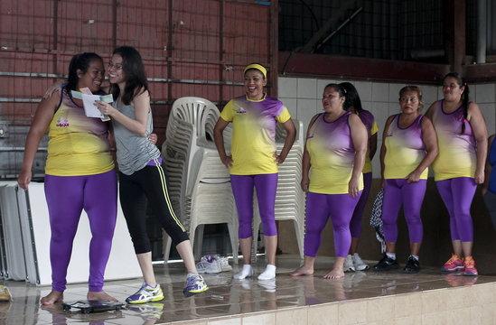 Andrea Abarca congratulates Hazel Castillo after announcing that she lost 7 kilograms, before an aerobics class in Los Guidos de Desamparados