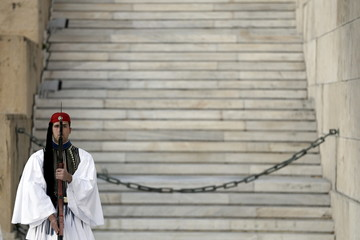 A Greek Presidential Guard presents arms as Palestinian President Abbas attends a wreath laying ceremony at the Tomb of the Unknown Soldier in Athens