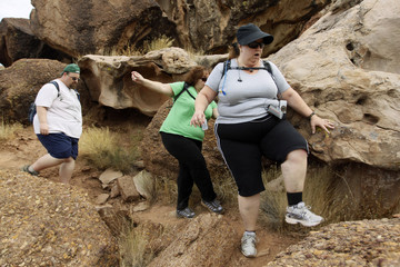 Guests Jerry Murray Freyja Pereira and Martha Moore scramble over boulders on a hike through the rugged terrain at the Biggest Loser Resort in Ivins