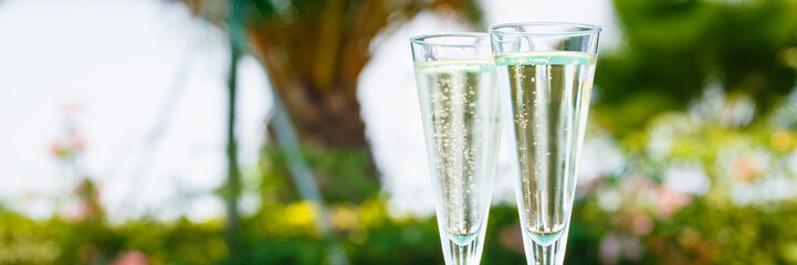 Two glasses of prosecco   at the edge of a resort pool. Concept of luxury vacation