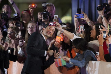 """Actor Adrien Brody poses with fans as he arrives on the red carpet for the film """"Septembers of Shiraz"""" during the 40th Toronto International Film Festival in Toronto"""