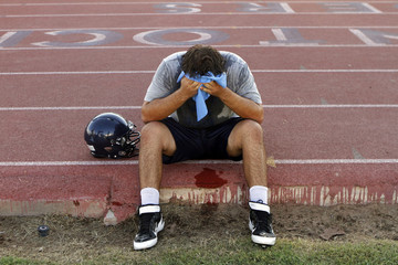 McClintock High School Chargers football player Joe Sanford holds an ice pack to his face after feeling light-headed during practice in Tempe