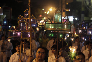 People, holding candles, attend a Via Crucis procession during Good Friday celebrations in Luque