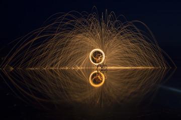Sparks Flying off Burning Steel Wool. Burning steel wool fireworks water reflection