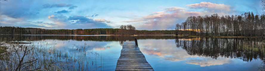 Wall Murals Blue Panorama landscape. Wooden pier on the lake at sunset, clouds reflection in the water.