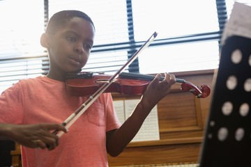 Boy playing violin while sitting in classroom