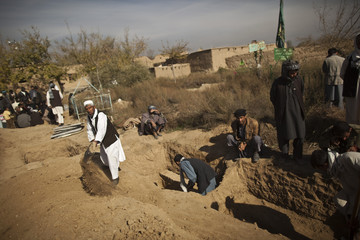 People dig graves for the victims of a fuel tanker blast in Parwan province