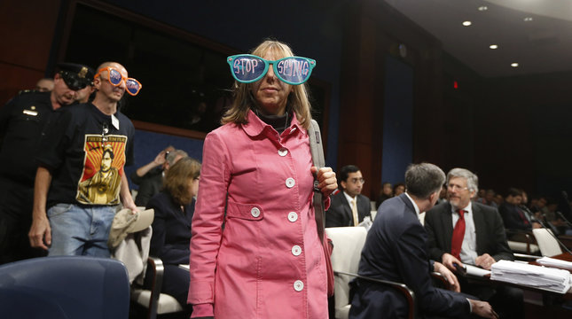 Codepink protester Medea Benjamin wears prop sunglasses as she and a partner are escorted from a House Intelligence Committee hearing on Capitol Hill in Washington