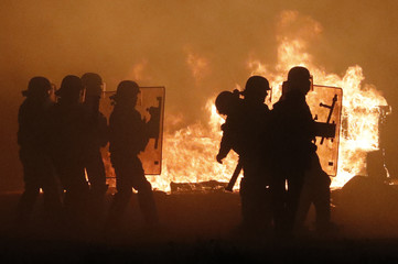 """French CRS police are seen in silhouette with flames from burning debris on the eve of the evacuation and transfer of migrants to reception centers in France, and the dismantlement of the camp called the """"Jungle"""" in Calais"""