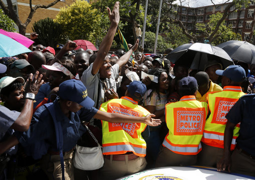 Frustrated mourners gather behind police cordons after being denied entry to the site where former South African President Nelson Mandela was lying in state in Pretoria