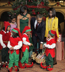 "U.S. President Barack Obama carries a basket of books next to his family as they greet children, dressed as elves, at the ""Christmas in Washington"" celebration in Washington"