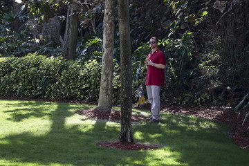 A Secret Service agent stands watch in the shade of some trees at Donald Trump's Mar-a-Lago Club during a campaign event in Palm Beach