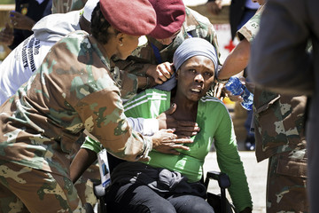 Soldiers assist a woman who collapsed after viewing the coffin of former South African President Nelson Mandela as he lies in state at the Union Buildings in Pretoria