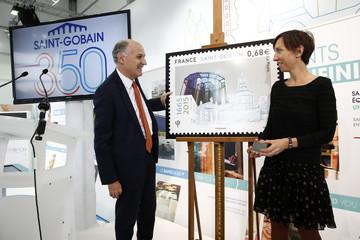 "Saint-Gobain Chairman and CEO Pierre-Andre de Chalendar and engraver Elsa Catelin present a commemorative postage stamp during a visit at the ""Future Sensations"" exhibition at the Place de la Concorde"