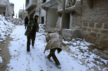 Free Syrian Army fighters play with snow near Aleppo International Airport in Aleppo