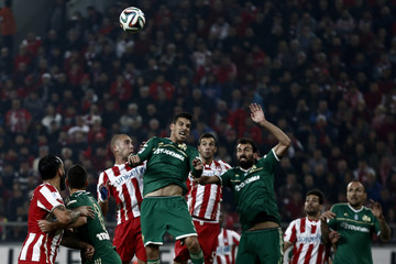 Olympiakos' and Panathinaikos' players jump for the ball during their Greek Super League soccer match at Karaiskaki stadium in Piraeus, near Athens,