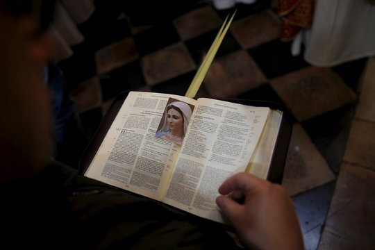 A worshipper holds an opened Bible during a Palm Sunday procession at the Church of the Holy Sepulchre in Jerusalem's Old City