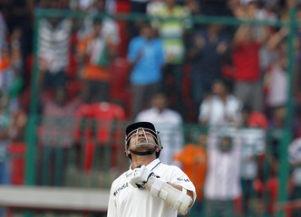 India's Tendulkar reacts after he scored a record of 14,000 test-run during the second test cricket match against Australia in Bangalore