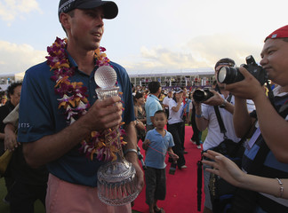 Kuchar of the U.S. poses for pictures with his team's trophy after winning the Mission Hills World Celebrity Pro-Am golf tournament in Haikou