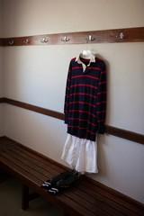 Rugby uniform hanging over shoes in locker room