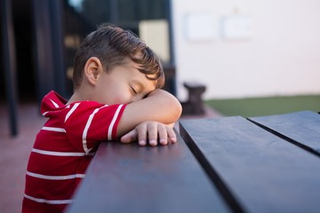 Close up of boy sleeping on table