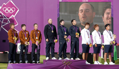 Italy's team listen to their national anthem during the men's archery victory ceremony at the Lords Cricket Ground during the London 2012 Olympics Games