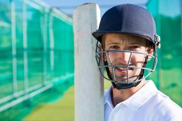 Portrait of cricket player with bat wearing helmet