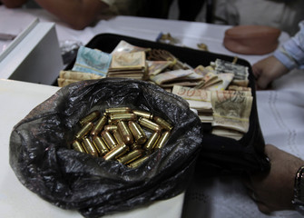 SENAD officials display confiscated money and ammunition, found during the arrest of suspected drug trafficker Soligo of Brazil, at a news conference in Asuncion