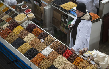 A vendor sells fruits and nuts at the Green Bazaar in Almaty