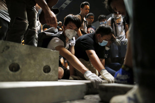 Pro-democracy protesters lay bricks inside a vehicle tunnel to block traffic leading to the financial Central district in Hong Kong
