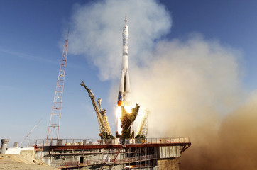The Soyuz TMA-11M spacecraft decorated with the 2014 Sochi Winter Olympic Games logo and a blue-and-white snowflake pattern, blasts off from the launch pad at the Baikonur cosmodrome