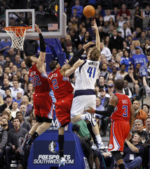 Dallas Mavericks forward Nowitzki shoots the ball as he is defended by Los Angeles Clippers forward Martin and forward Griffin during their NBA basketball game in Dallas, Texas