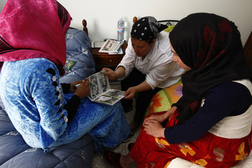 """Aida, an unmarried pregnant woman and rape victim, Wafa, a rape victim and Atika, a divorced woman abandoned by her family look at Wafa's photograph album at """"Dar al Insania"""" (Humanitarian House) in the eastern city of Annaba"""