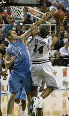 North Carolina forward Tyler Zeller works to defend against Georgia Tech forward Derrick Favors during a college basketball game in Greensboro