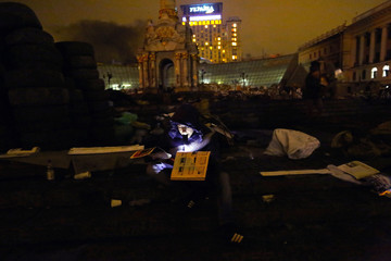 Anti-government protesters reads magazine in central Kiev