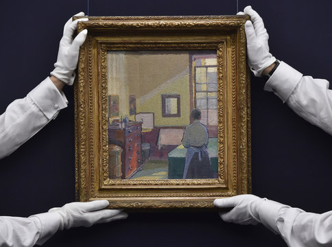 'Interior (Mrs Mounter)' by Harold Gilman, with an estimate of 150,000 GBP - 250,000 GBP, part of British pop star David Bowie's art collection, is held by assistants at a press view at Sotheby's auction house, in central London, Britain