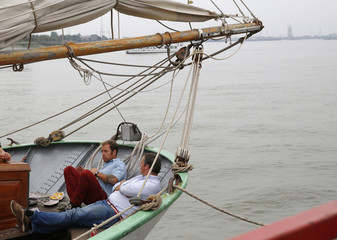 Men relax on-board a one of the tall ships moored on the bank of the River Thames at Woolwich in east London