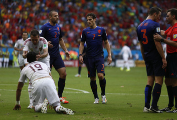 Spain's Costa is helped to his feet after being fouled by de Vrij of the Netherlands, as he argues with referee Rizzoli, during their 2014 World Cup Group B soccer match at the Fonte Nova arena in Salvador
