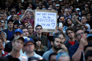 People attend a vigil in memory of victims one day after a mass shooting at the Pulse gay night club in Orlando, in Los Angeles