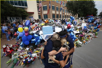 A softball team hugs after paying their respects at a makeshift memorial at Dallas Police Headquarters following the multiple police shootings in Dallas