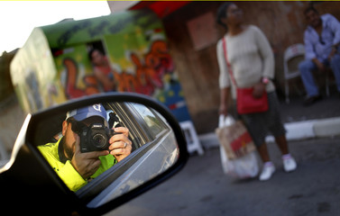 Pfaffenbach is reflected in his car's mirror as he takes pictures of the Ithakera neighbourhood  in Sao Paulo